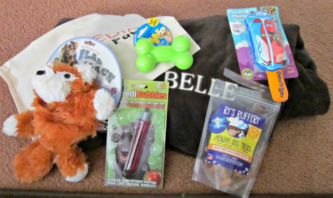 The contents of Belle's WOOFIPEDIA pack: Personalized AKC Fleece Blanket, Megalast Bone, Flap Jack Plush Toy, Ry's Ruffery Treats (peanut butter), Doggy Incredibubbles, and I got a free dog freeze toy (can't remember what it was called).