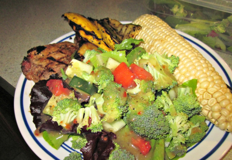 A delicious plate of food with a salad comprised of local greens and broccoli from the backyard.